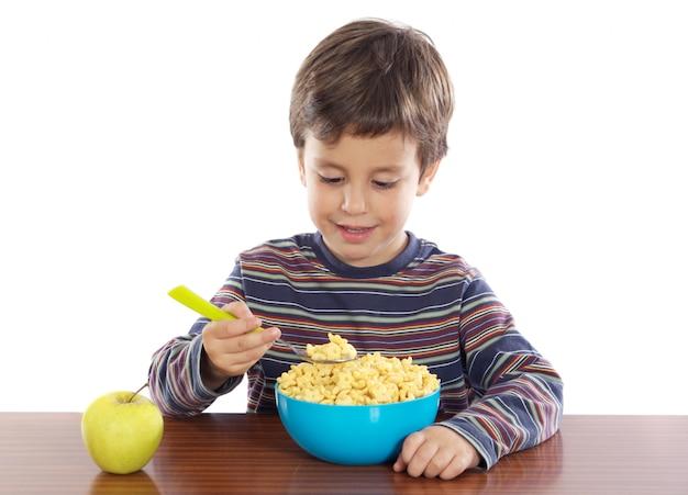 Aanbiddelijk kind dat a over witte achtergrond ontbijt