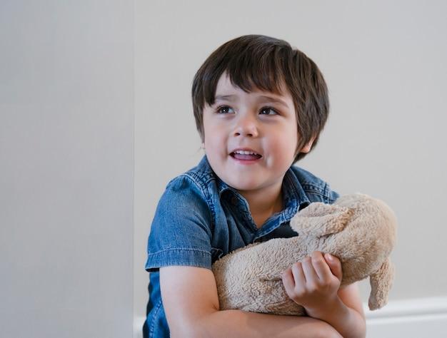 Aanbiddelijk kind dat met grote glimlach met zacht speelgoed thuis ontspant. positief kinderenconcept