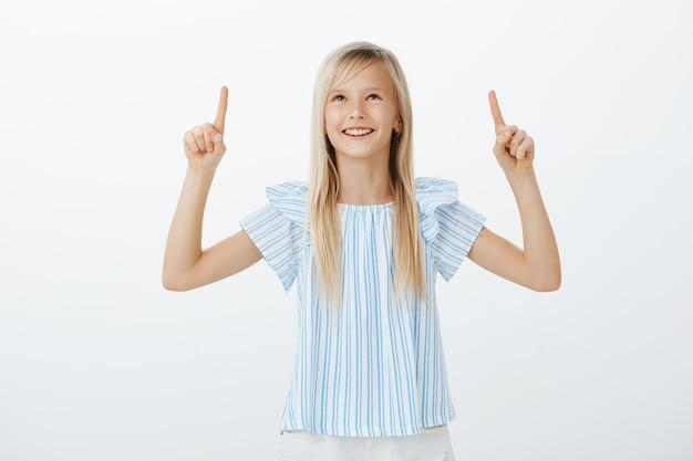 Aanbiddelijk kind dat wolkenvormen met vriend bespreekt. portret van creatief gelukkig jong meisje met blond haar, breed glimlachend van positieve emoties, op zoek en omhoog met opgeheven wijsvingers