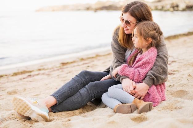 Aanbiddelijk kind en moeder die in openlucht koesteren