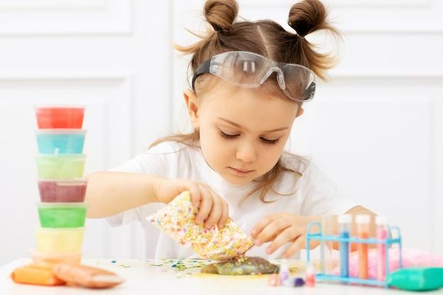 Aanbiddelijk kind in een wit t-shirt met twee staarten in een beschermende bril die pluizig slijm maakt van veelkleurige ingrediënten