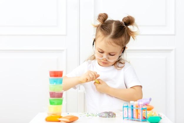 Aanbiddelijk kind in een wit t-shirt met twee staarten zit aan de tafel in een beschermende bril en doet experimenten, maakt pluizig slijm van veelkleurige ingrediënten
