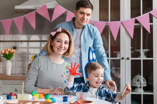 Aanbiddelijk kind met moeder en vader het stellen
