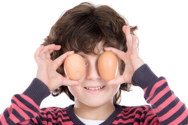 Aanbiddelijk kind met twee eieren op zijn ogen op een witte achtergrond
