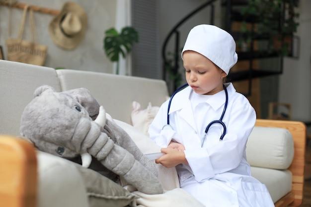 Aanbiddelijk kind verkleed als dokter die met speelgoedolifant speelt en zijn adem controleert met een stethoscoop.