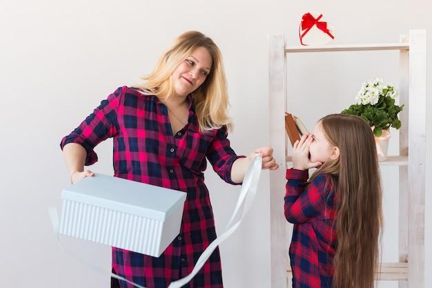 Aanbiddelijk kindmeisje dat met grote giftdoos het aan haar moeder geeft