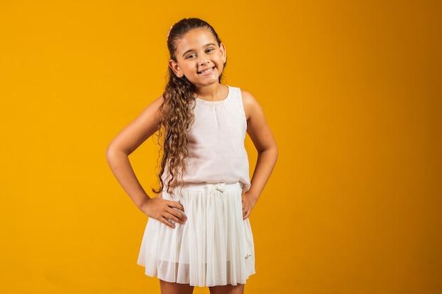 Aanbiddelijk kindmeisje met lang golvend haar dat gelukkig bij camera glimlacht