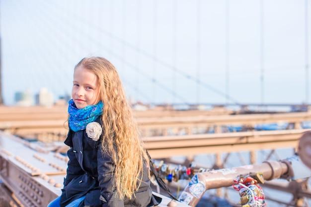Aanbiddelijk klein kind bij brooklyn bridge in de stad van new york met mening over de weg