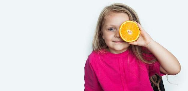 Aanbiddelijk klein meisje bedekt haar oog met een sinaasappel die vooraan op een witte muur met vrije ruimte glimlacht