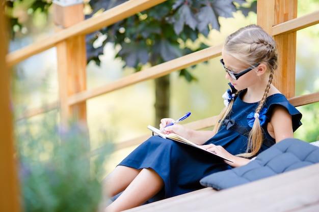 Aanbiddelijk klein schoolmeisje met nota's en potloden openlucht. terug naar school.