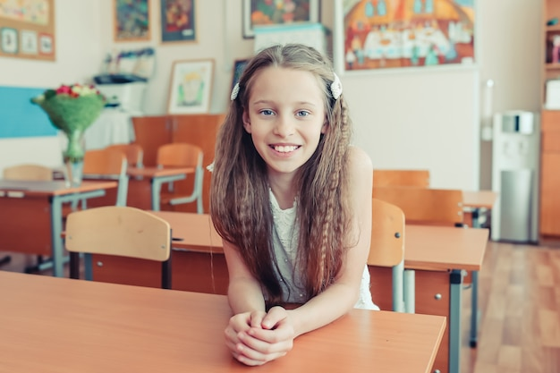 Aanbiddelijk klein schoolmeisje met nota's en potloden openlucht.