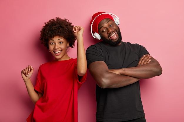Aanbiddelijk krullend meisje glimlacht en danst op muziek samen met mannelijke kameraad, geniet van samen tijd doorbrengen, geïsoleerd op roze muur. zorgeloze hipster met gekruiste armen