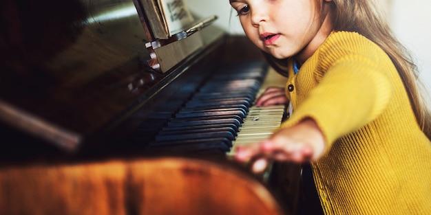 Aanbiddelijk leuk meisje het spelen pianoconcept