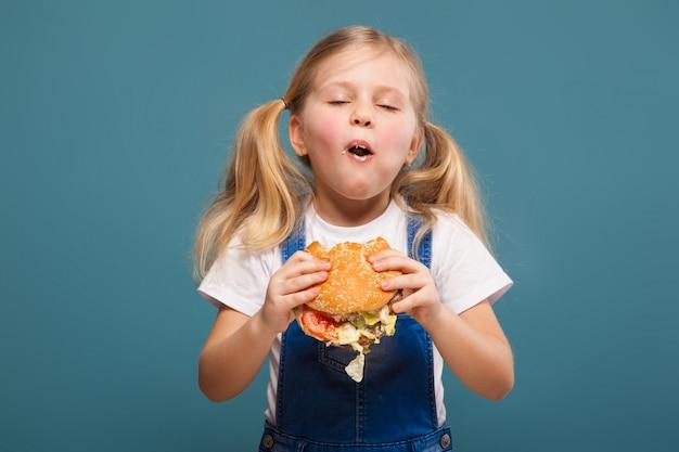 Aanbiddelijk leuk meisje in wit overhemd en jean jumpsuit met hamburger