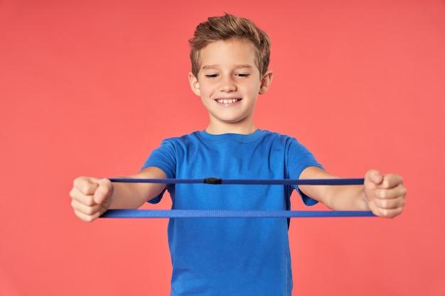 Aanbiddelijk mannelijk kind dat weerstandsoefenband vasthoudt en glimlacht terwijl hij tegen een rode achtergrond staat