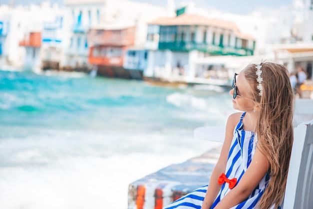 Aanbiddelijk meisje bij oude straat van typisch grieks traditioneel dorp op mykonos