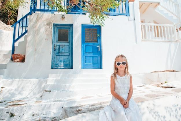 Aanbiddelijk meisje bij oude straat van typisch grieks traditioneel dorp