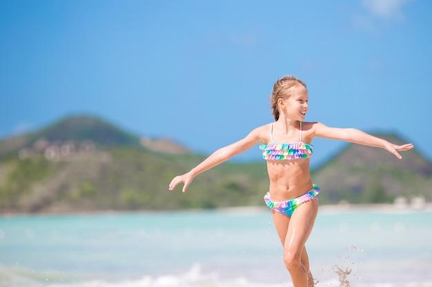 Aanbiddelijk meisje bij strand dat heel wat pret in ondiep water heeft