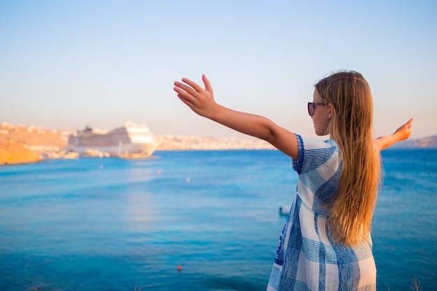 Aanbiddelijk meisje bij strand grote lainer als achtergrond in griekenland