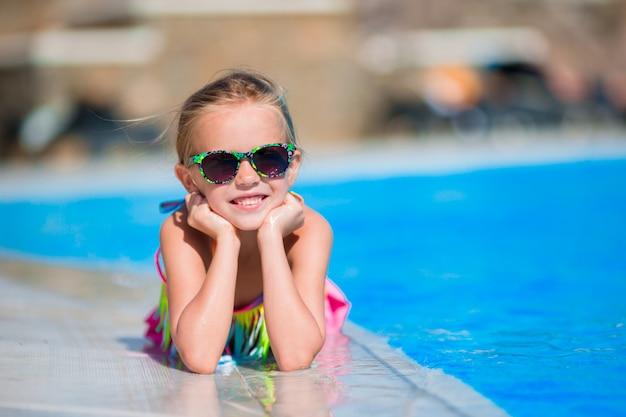 Aanbiddelijk meisje bij zwembad dat pret heeft tijdens de zomervakantie