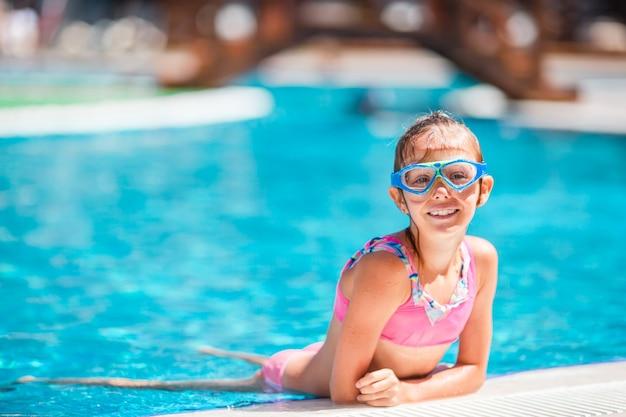 Aanbiddelijk meisje dat bij openlucht zwembad zwemt