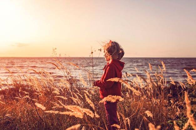 Aanbiddelijk meisje dat de zonsondergang op het overzees bekijkt
