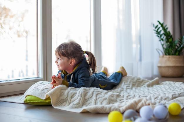 Aanbiddelijk meisje dat door het raam kijkt, liggend op een wollen deken. het is sneeuw en koud buiten.