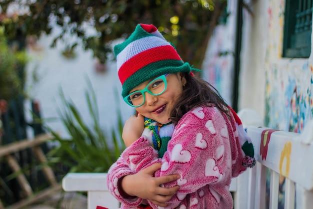Aanbiddelijk meisje dat en haar sneeuwmanstuk speelgoed glimlacht houdt