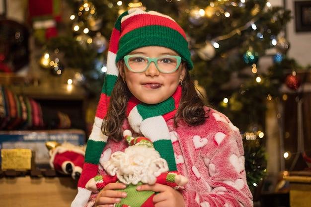 Aanbiddelijk meisje dat en haar stuk speelgoed van de kerstman glimlacht houdt