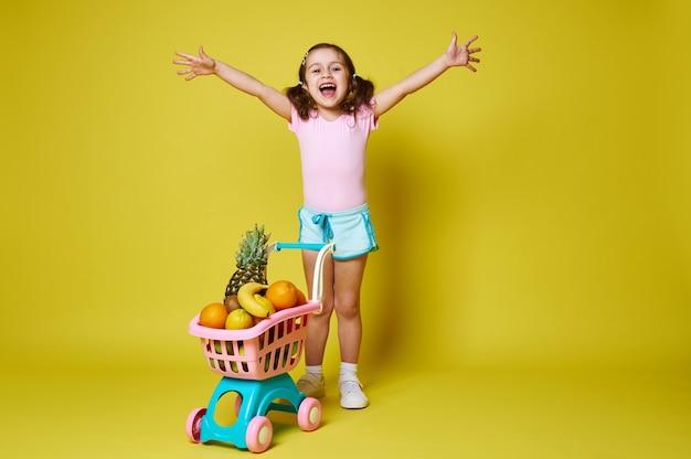 Aanbiddelijk meisje dat haar armen opheft en geluk uitdrukt dat zich dichtbij een winkelwagentje vol met exotisch fruit op geel met exemplaarruimte bevindt