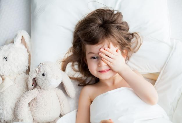 Aanbiddelijk meisje dat haar ogen achter haar handen verbergt toen ze wakker werd. ze ligt in een wit bed met konijnenspeelgoed.