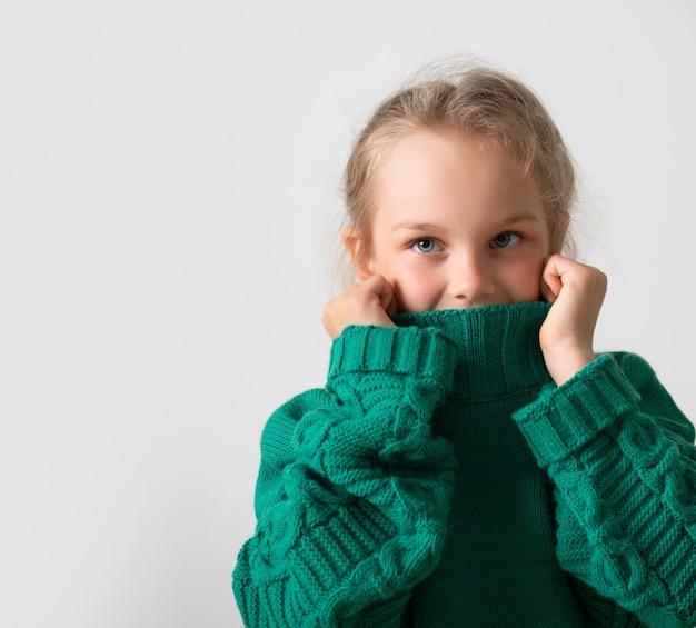 Aanbiddelijk meisje dat het onderste deel van haar gezicht verbergt onder een dikke kraag van een warme gebreide trui.