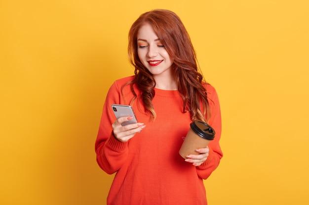 Aanbiddelijk meisje dat het oranje sweater dragen geïsoleerd stelt, koffie houdt om mee te nemen en mobiele telefoon