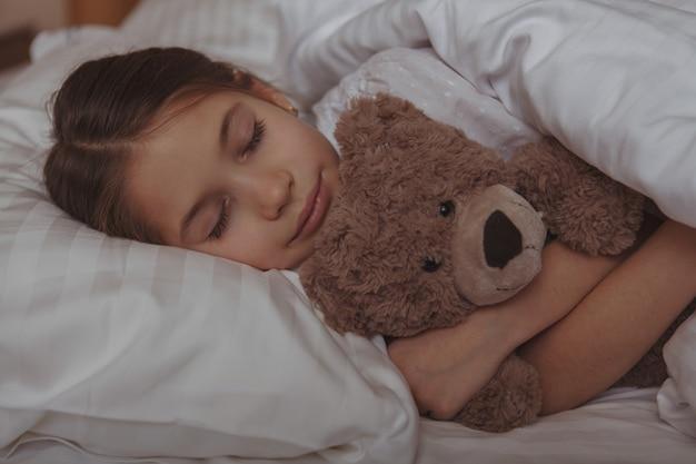 Aanbiddelijk meisje dat in bed thuis ligt