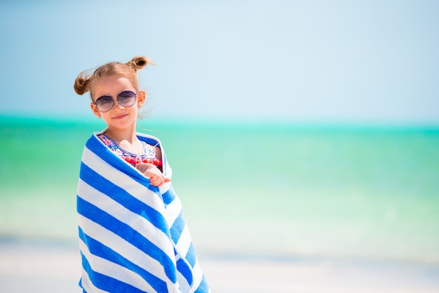 Aanbiddelijk meisje dat in handdoek wordt verpakt na het zwemmen bij tropisch strand
