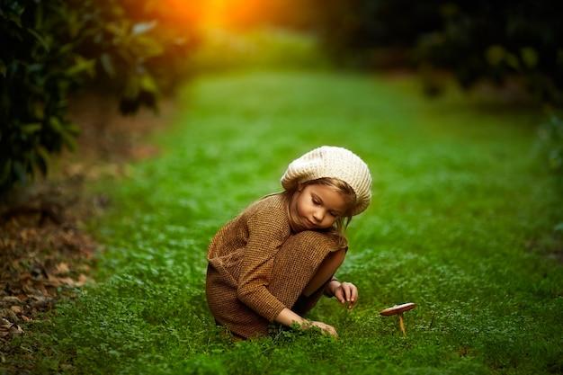 Aanbiddelijk meisje dat in het bos op de zomerdag wandelt