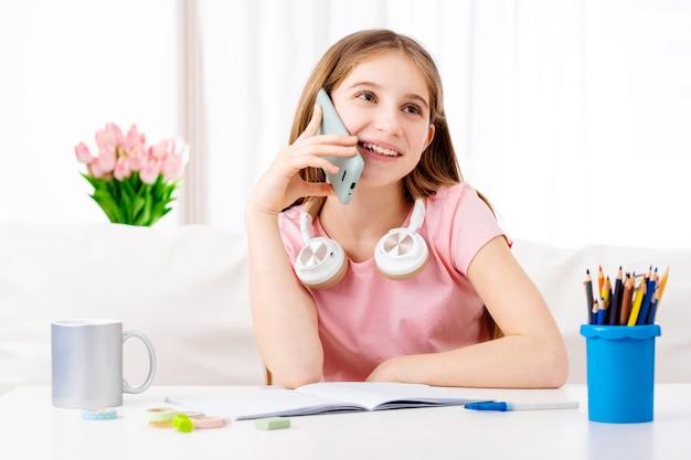 Aanbiddelijk meisje dat in vrije tijd telefoneert naar haar schoolvrienden