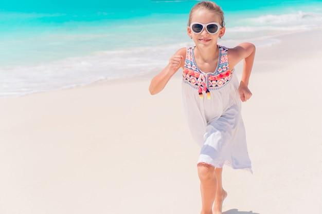 Aanbiddelijk meisje dat langs wit zand caraïbisch strand loopt