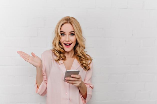 Aanbiddelijk meisje dat met in hand telefoon positieve emoties uitdrukt. aantrekkelijke blonde vrouw in katoenen roze nachtkleding met smartphone in de buurt van dichtgemetselde muur.