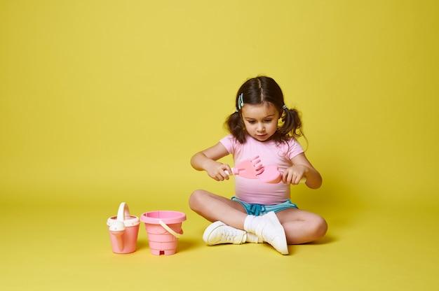 Aanbiddelijk meisje dat met schop en hark speelt, dichtbij een reeks strandspeelgoed zit.