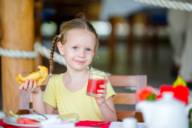 Aanbiddelijk meisje dat ontbijt heeft bij openluchtkoffie