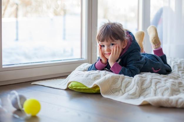 Aanbiddelijk meisje dat op een wollen deken dichtbij het venster ligt, het is buiten de sneeuwwinter