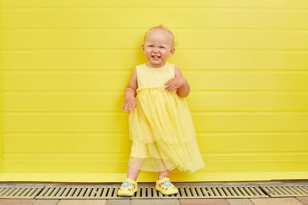 Aanbiddelijk meisje dat op gele achtergrond glimlacht.