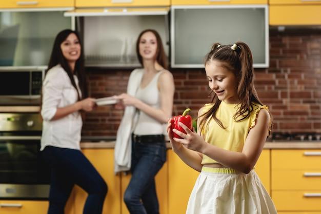 Aanbiddelijk meisje dat paprika houdt en het bekijkt. gelukkig meisje dat zich in de keuken bevindt en met een grote paprika speelt. op de achtergrond stapelen twee vrouwen schotels