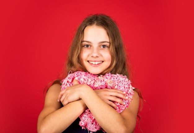 Aanbiddelijk meisje dat pret heeft. romantische stemming. gelukkig kind houdt hart rode achtergrond vast. vakantie van liefde en zorg. meisje met roze hart. hartvormige decor valentijnsdag. geliefd voelen. schattige baby.