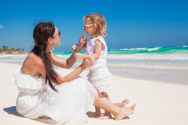 Aanbiddelijk meisje dat pret met haar jonge moeder op het witte zandige strand in tulum, mexico heeft