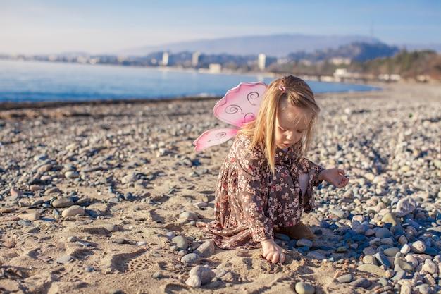 Aanbiddelijk meisje dat pret op het strand in een de winter zonnige dag heeft