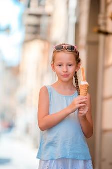 Aanbiddelijk meisje dat roomijs in openlucht bij de zomer eet. leuk jong geitje dat van echte italiaanse gelato geniet dichtbij gelateria in rome