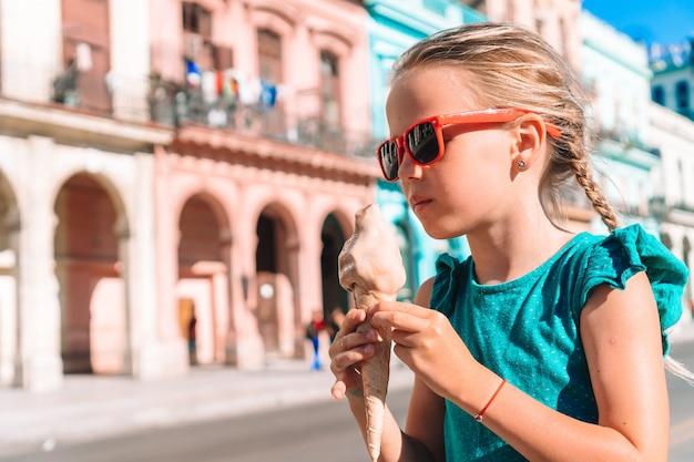 Aanbiddelijk meisje dat roomijs op populair gebied in oud havana, cuba eet.