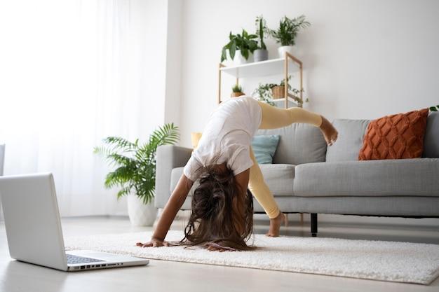 Aanbiddelijk meisje dat thuis yoga doet